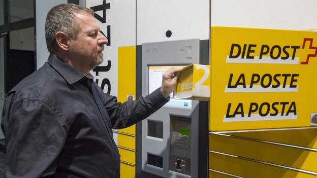Ein Mitarbeiter der Schweizerischen Post an einem Automaten.