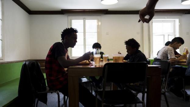 Jugendliche Asylsuchende an einem Tisch.