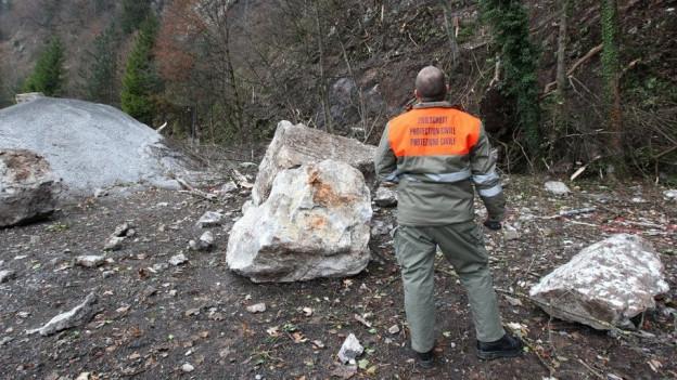 Mann vom Zivilschutz steht vor einem Felssturz.
