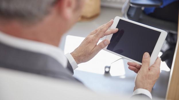 Ein Mann schaut auf sein Tablet.