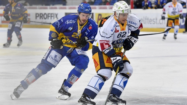 Zwei Eishockeyspieler kämpfen um einen Puck.
