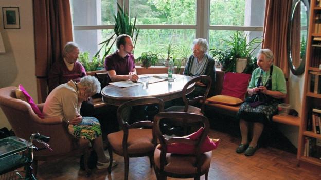 Alte Menschen sitzen an einem Tisch.