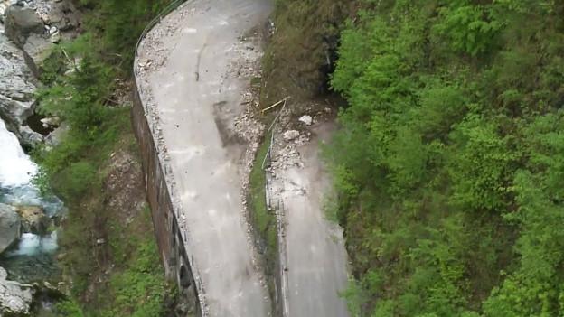 Strasse, die von einem Felssturz verschüttet worden ist.