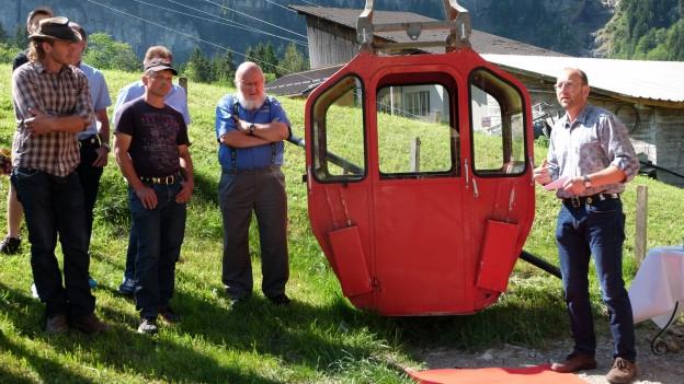 Mehrere Männer stehen bei einer roten Kabine einer Kleinseilbahn.