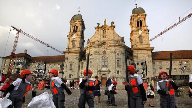 Menschen vor Klosterfassade Einsiedeln.