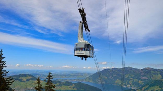 Luftseilbahn fährt mit Bergen im Hintergrund.