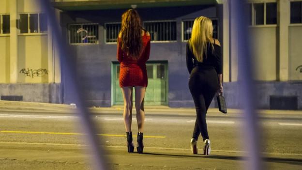 Zwei Prostituierte stehen nachts auf einer Strasse