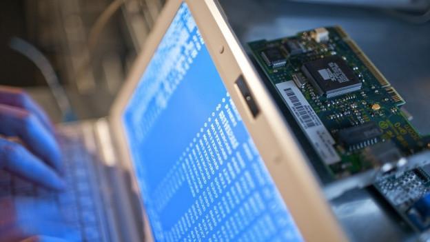 Laptop von oben fotografiert, dahinter Innereien eines Computers.