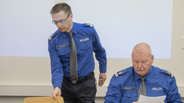 Zwei Polizisten setzen sich an einen Tisch.