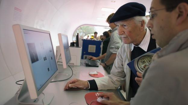 Ein alter Mann bedient unter Anleitung einen Computer.
