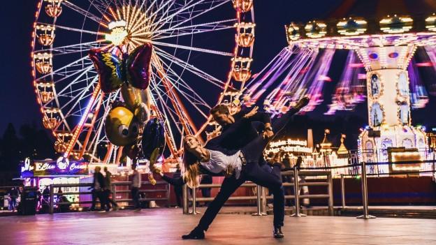 Ein Mann und eine Frau tanzen auf dem Europaplatz in Luzern. Im Hintergrund ein farbig beleuchtetes Riesenrad.