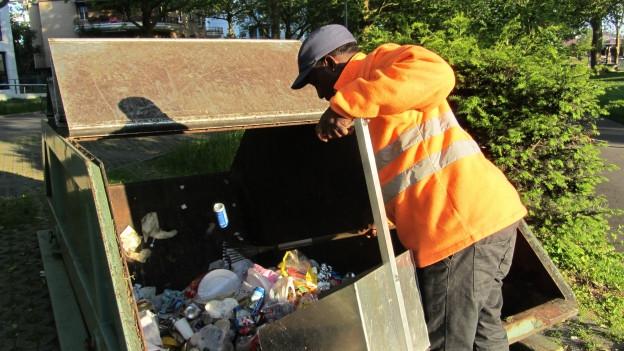 Ein Flüchtling entsorgt Abfall in einem grossen Container.