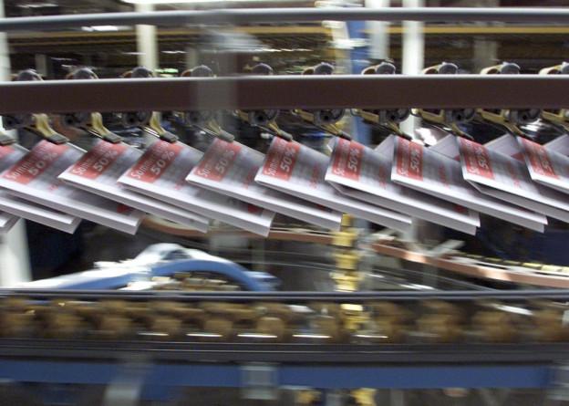 Eine Druckmaschine befördert frisch gedruckte Zeitungen