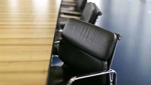 Freie Stühle an einem Sitzungstisch.