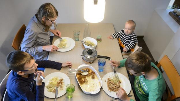 Eine Familie sitzt beim Essen am Tisch.
