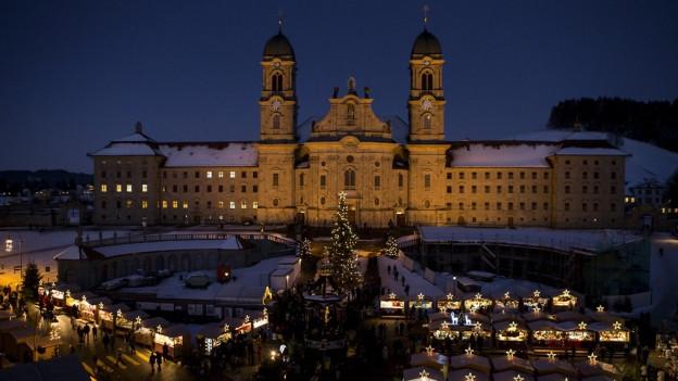 Klosterplatz Einsiedeln im Winter mit Weihnachtsmarkt.