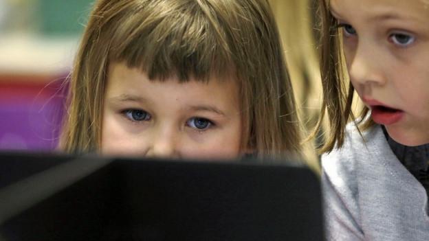 Kinder blicken auf einen Laptop.
