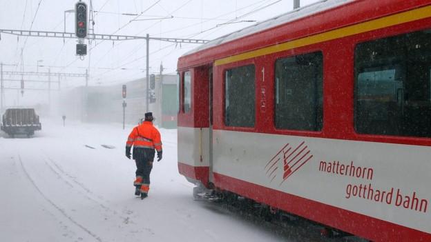 Zug steht in einem schneebedeckten Bahnhof.