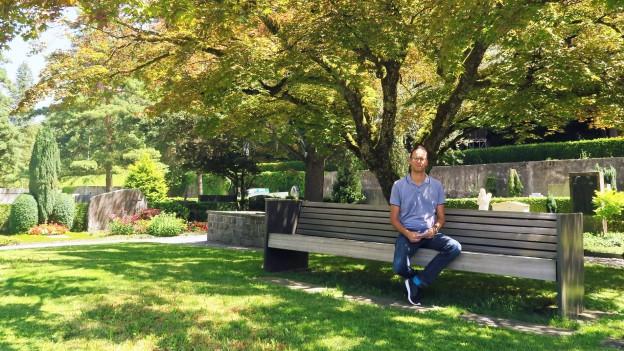 Ein Mann sitzt auf einer Bank auf einem Friedhof in der Stadt Luzern.