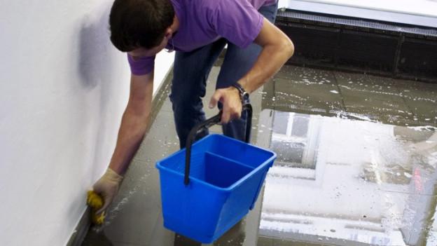 Ein Hausabwart putzt einen Boden.