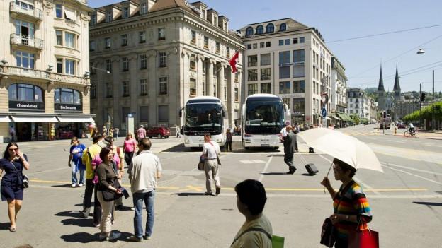 Reisebusse bringen Touristen vor die Juwelierläden am Schwanenplatz