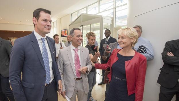 Gelöste Stimmung bei den drei FDP-Bundesratskandidaten Maudet, Cassis und Moret (von links) vor dem Podium in Zug