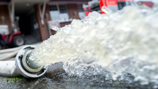Ein Feuerwehrschlauch, aus dem abgepumptes Wasser läuft.