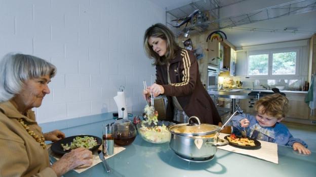 eine Frau, eine Grossmutter und ein Knabe sitzen an einem Tisch und essen, während die Mutter noch das Essen schöpft.