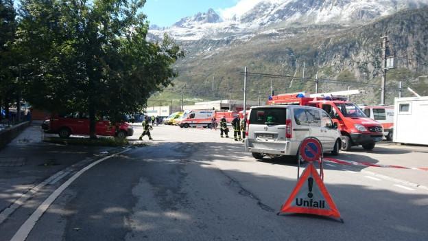 Ein oranges Unfalldreieck auf einer Strasse. Im Hintergrund Polzei- und Feuerwehrautos, links ein Baum.
