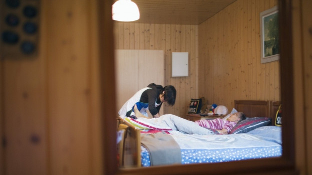 Pflegerin pflegt Frau in einem Bett.
