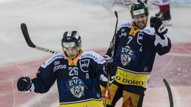 Zwei Eishockeyspieler triumphieren.