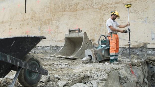Ein Bauarbeiter bei Messungen auf einer Baustelle.