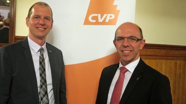 Die beiden CVP Kandidaten Christoph Amstad und Michael Siegrist stehen vor dem CVP-Logo