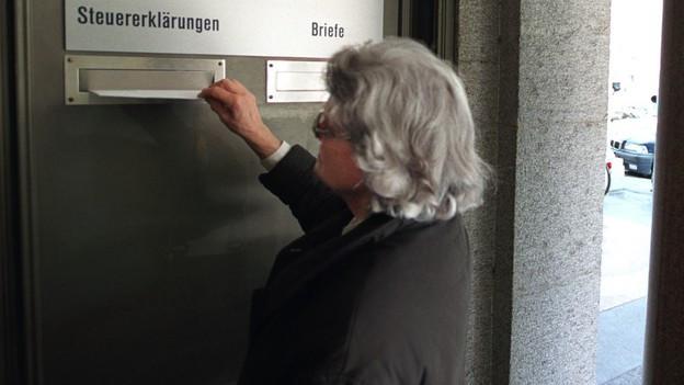 Eine Frau wirft ein Couvert in einen Briefkasten.