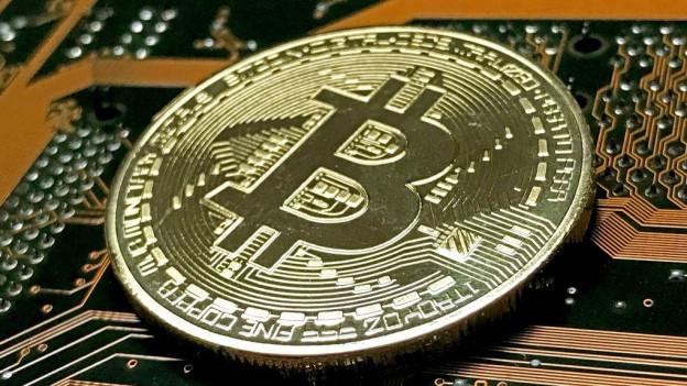 Ein symbolischer Bitcoin auf einer Computer-Grundplatine.