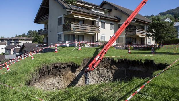 Ein grosses Loch klafft im Boden vor einem Wohnhaus.