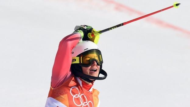 Eine Frau im Skidress schliesst die Augen.