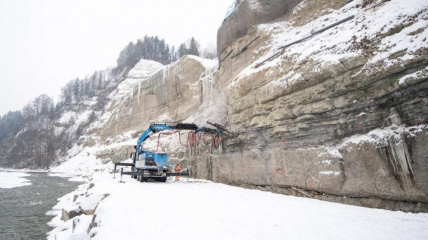 Eine Maschine steht im Schnee vor einer Felswand.