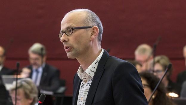 Mann an Mikrofon in Parlamentssaal