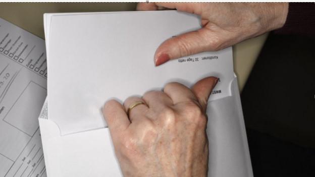Ein Frau öffnet einen Brief (Symbolbild)