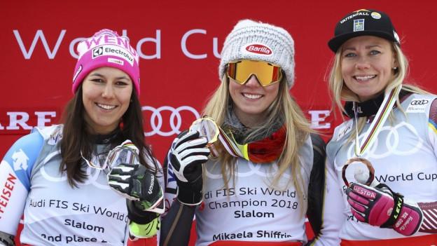 Drei Skifahrerinnen stehen auf dem Podest mit ihren Medaillen