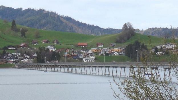 Ein Viadukt über einen kleinen See, am Ufer ein Dorf.