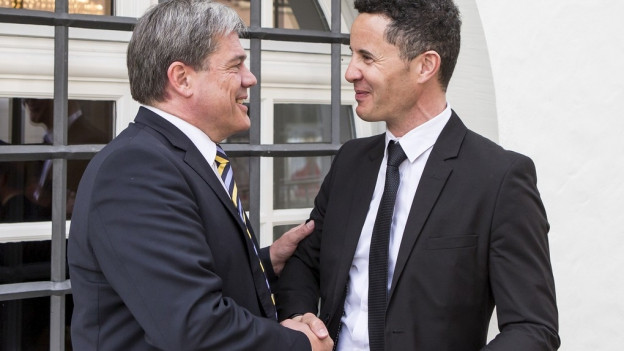 Zwei Männer in Anzügen reichen sich die Hand.