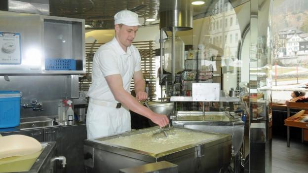 Käser bearbeitet die Milch in einem grossen Kessel.