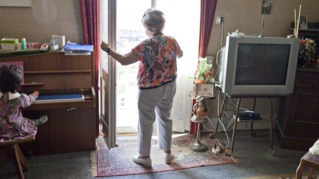 Alte Frau steht am Fenster.