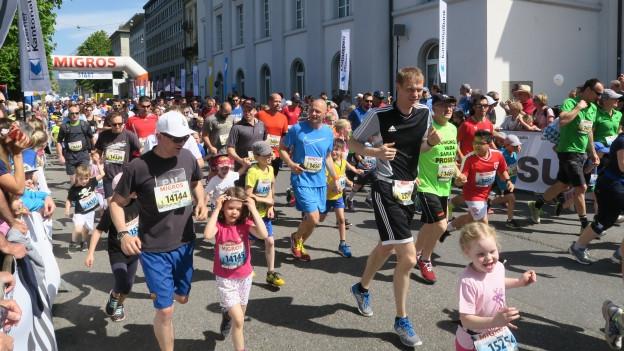 Sowohl Erwachsene wie auch Kinder springen in sportliche Kleidung.