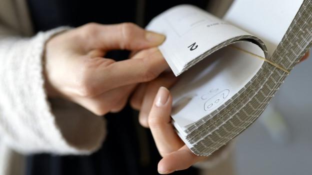 Eine Person hält ein Bündel Abstimmungsunterlagen in den Händen.