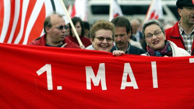 """Leute an der 1.-Mai-Demonstration 2006 in Luzern. Sie halten ein grosses, rotes Transparent mit der Aufschrift """"1. Mai""""."""