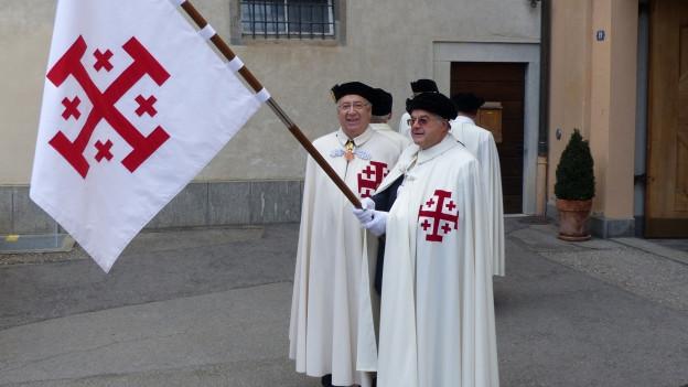Männer halten eine Fahne hoch.