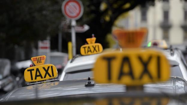 Mehrere Taxis mit Leuchtschrift auf dem Dach warten auf Kundschaft.